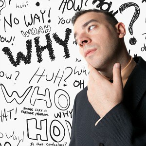 a man thinking with lots of questions on a board behind hiim