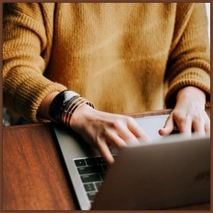 girl in a sweater typing on a laptop